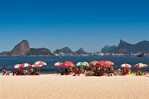 Niteroi, Rio de Janeiro, Brazil - April 6, 2014: Group of people relaxing in Icarai beach in Niteroi. In the horizon - a scenic view of Rio de Janeiro mountains.